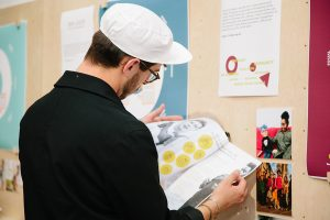 Visitor looks at illustrations produced by one of the entrepreneurs in the Ways of Working exhibition