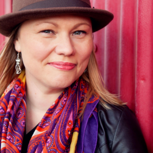 Image of Amy Morse wearing a hat and vibrant scarf