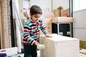 A young boy in a stripey shirt taps a box with a wooden mallet