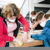 The photograph is taken in a busy Factory, with two people, one child and one adult, sanding down a round piece of wood together.